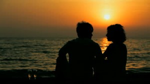 stock-footage-silhouette-of-young-man-and-woman-sitting-on-the-beach-and-talking-to-each-other-beautiful-sunset